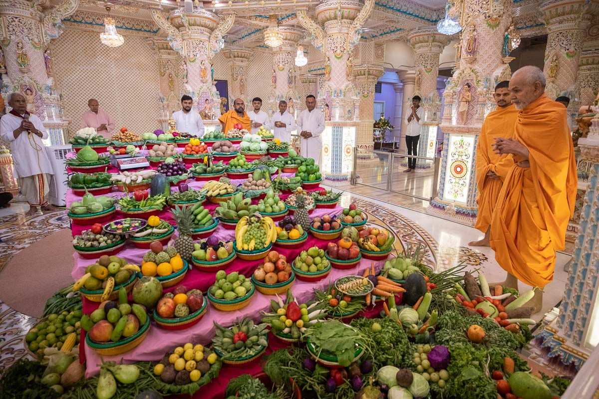 Param Pujya Mahant Swami Maharaj observes the annakut of fruits and vegetables offered to Shri Nilkanth Varni