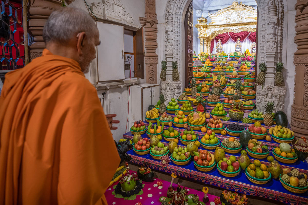 Swamishri engrossed in darshan of the annakut of fruits