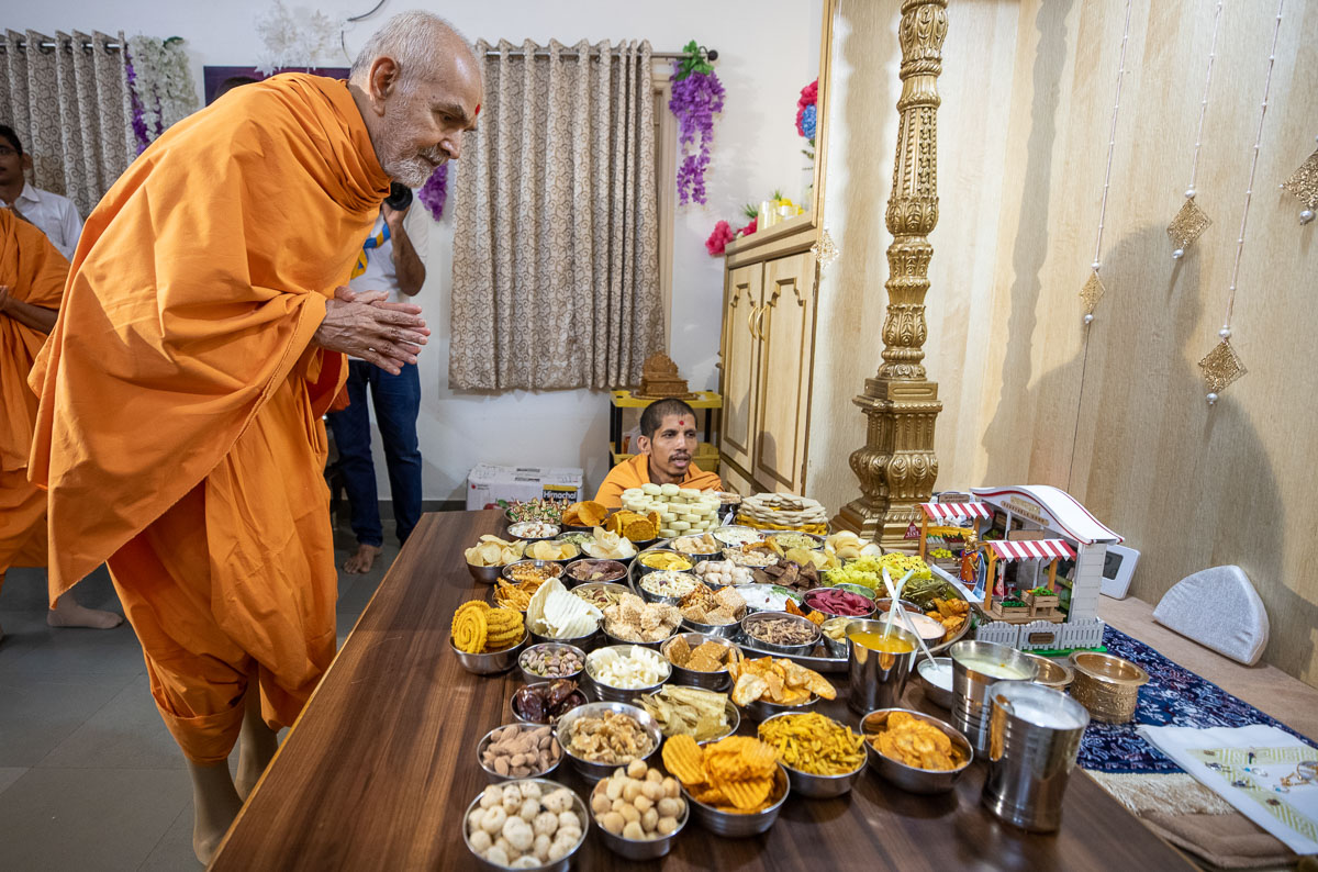 Swamishri engrossed in darshan of the thal offered to Shri Harikrishna Maharaj