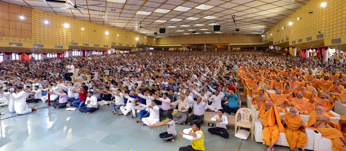 Sadhus and devotees gesture to embrace Swamishri