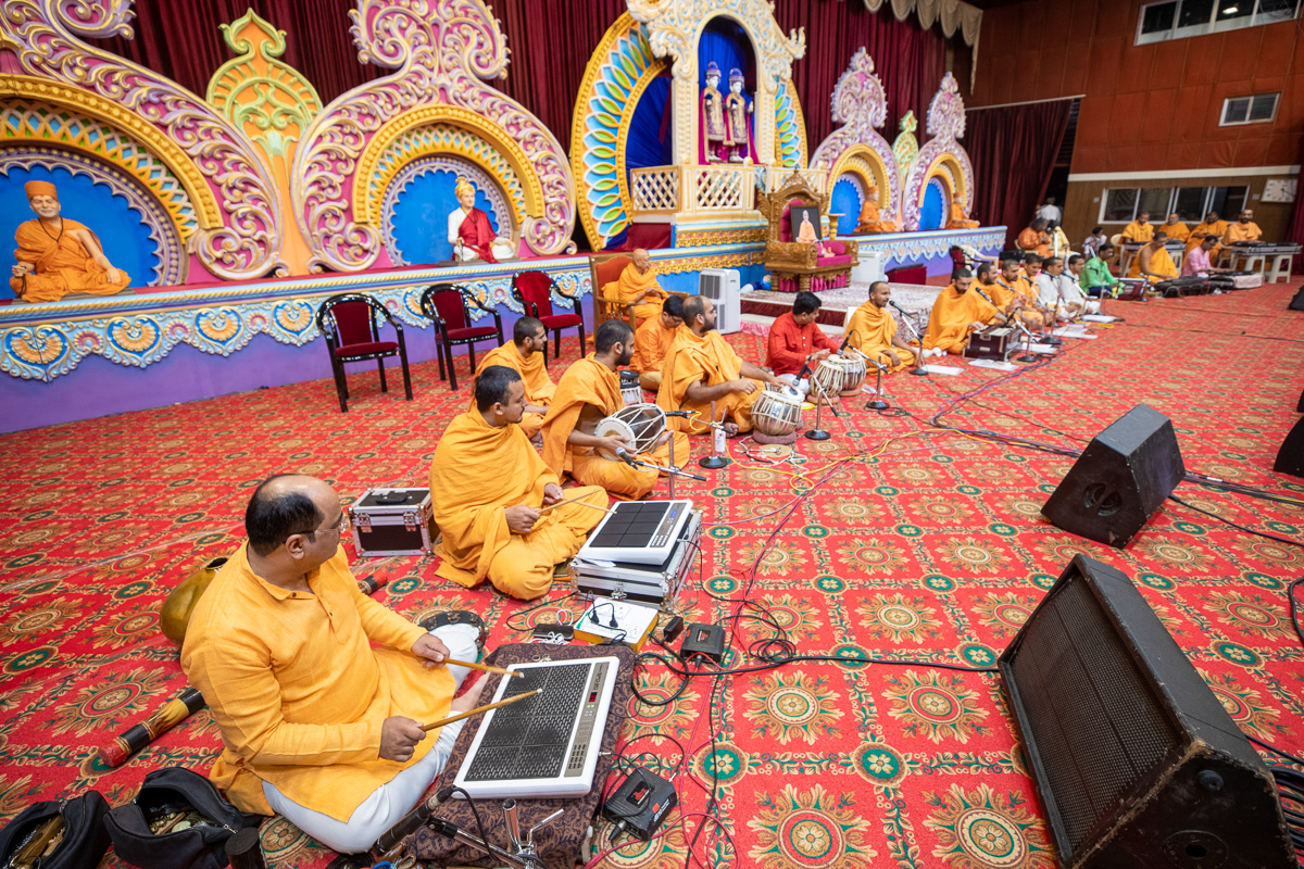 Sadhus and youths present a kirtan aradhana