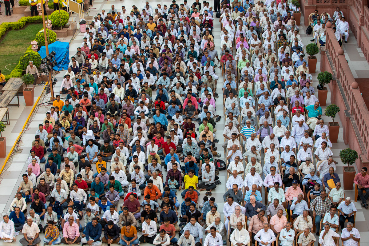 Devotees seated in the mandir grounds listening to the kirtan aradhana