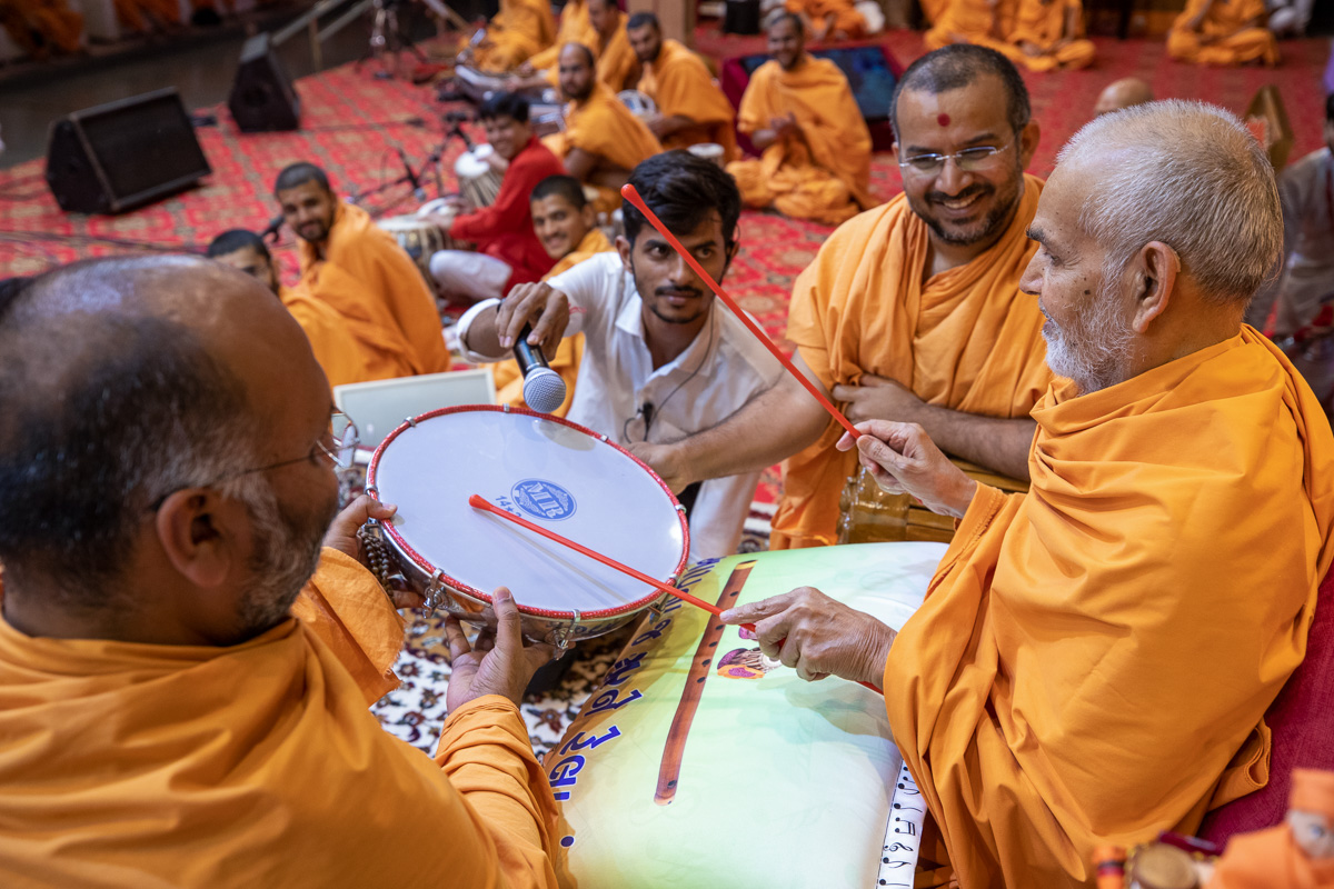 Swamishri plays on a drum