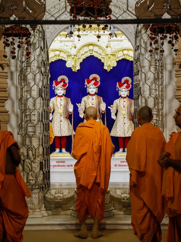 Swamishri engrossed in darshan of Bhagwan Swaminarayan, Aksharbrahman Gunatitanand Swami and Shri Gopalanand Swami in the evening