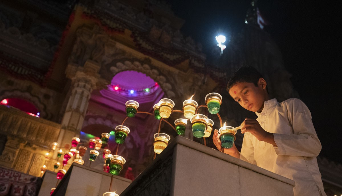 A child lights a divo in preparation for Swamishri's arrival