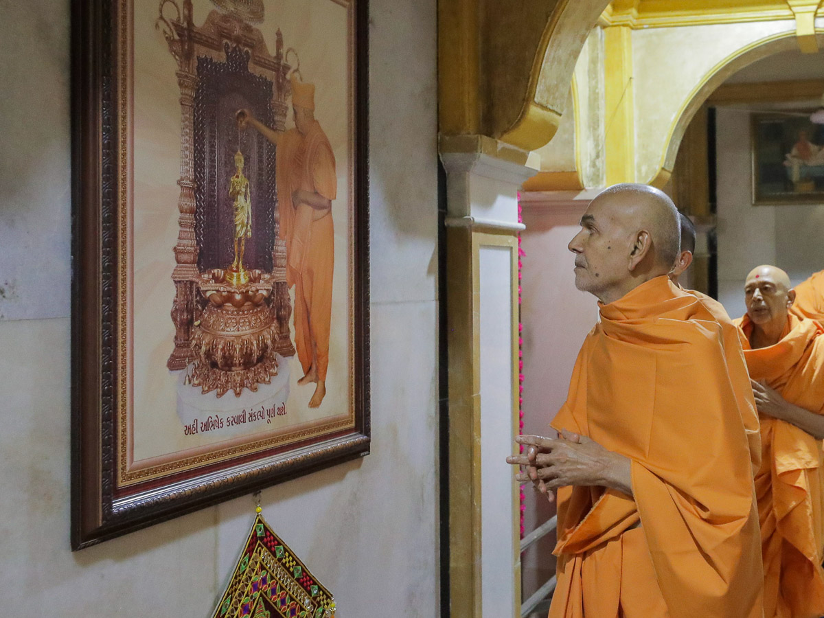Swamishri observes a photo