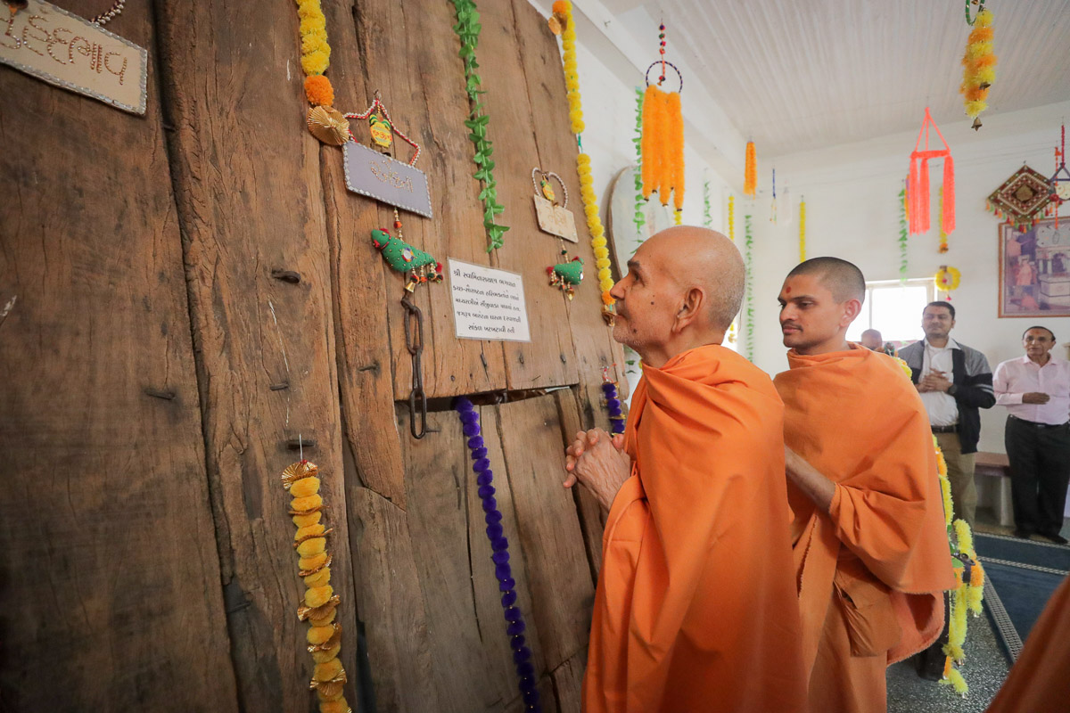 Swamishri engrossed in darshan of the door of Jagrup Barot's house in Sinjiwada (Kutch) sanctified by Bhagwan Swaminarayan