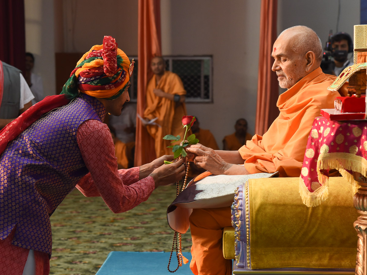 A youth presents a flower to Swamishri