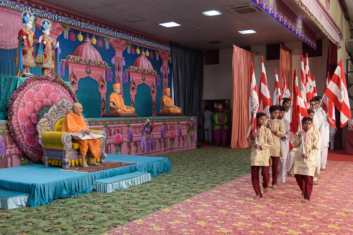 Children perform a parade in the evening satsang assembly