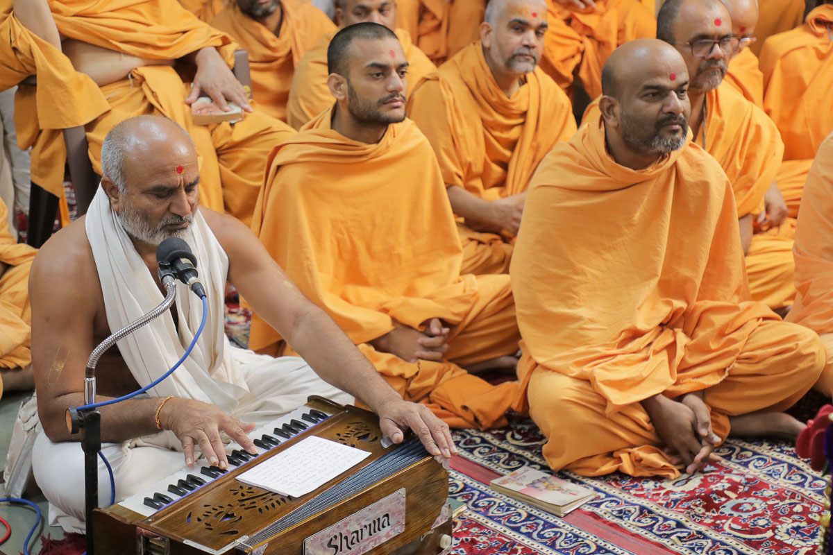 A parshad sings a kirtan in Swamishri's daily puja