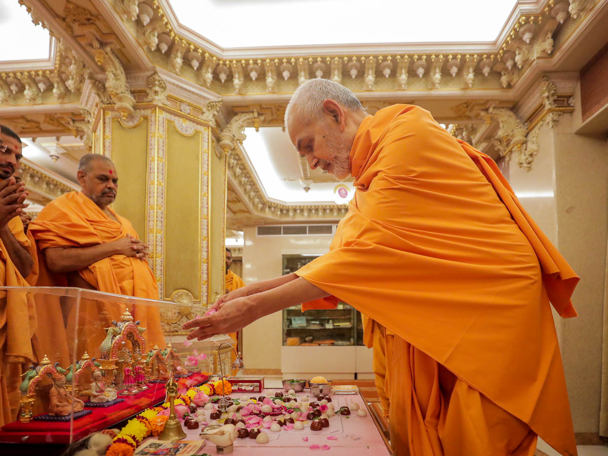 Swamishri offers flower petals in the mahapuja
