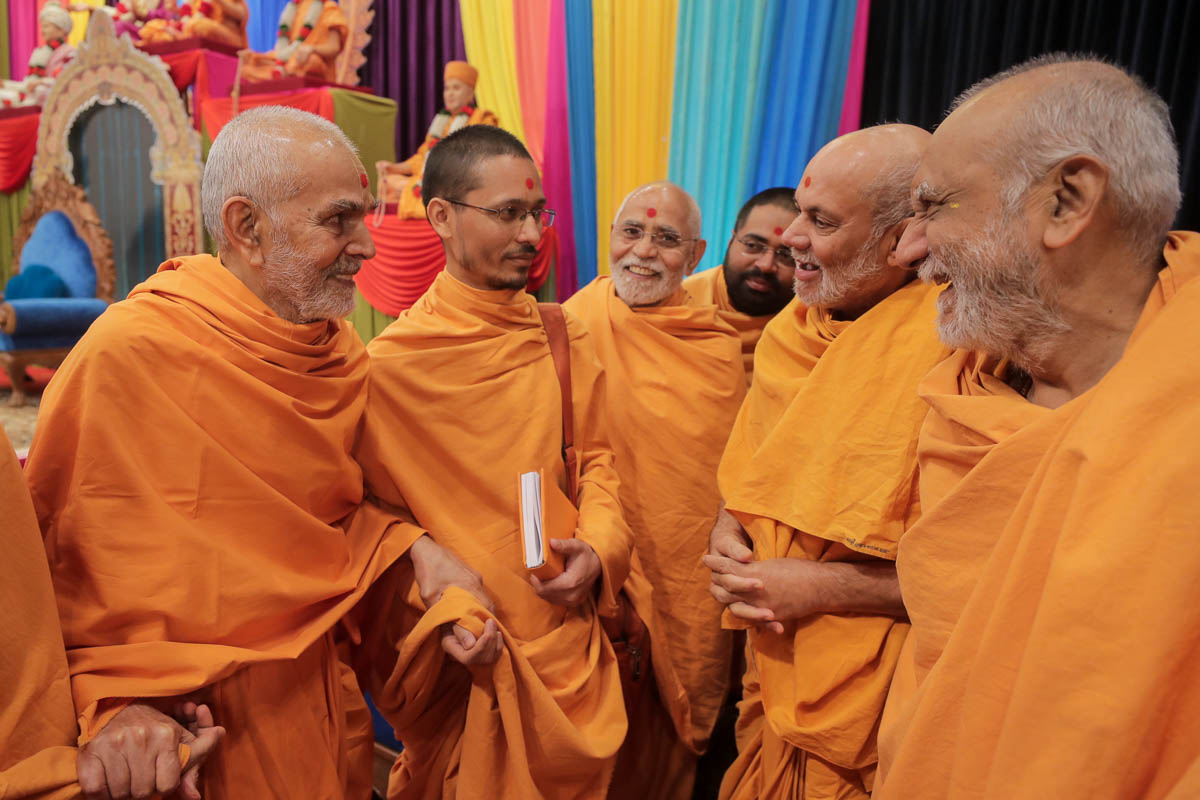 Swamishri shares a light moment with Pujya Viveksagar Swami and sadhus