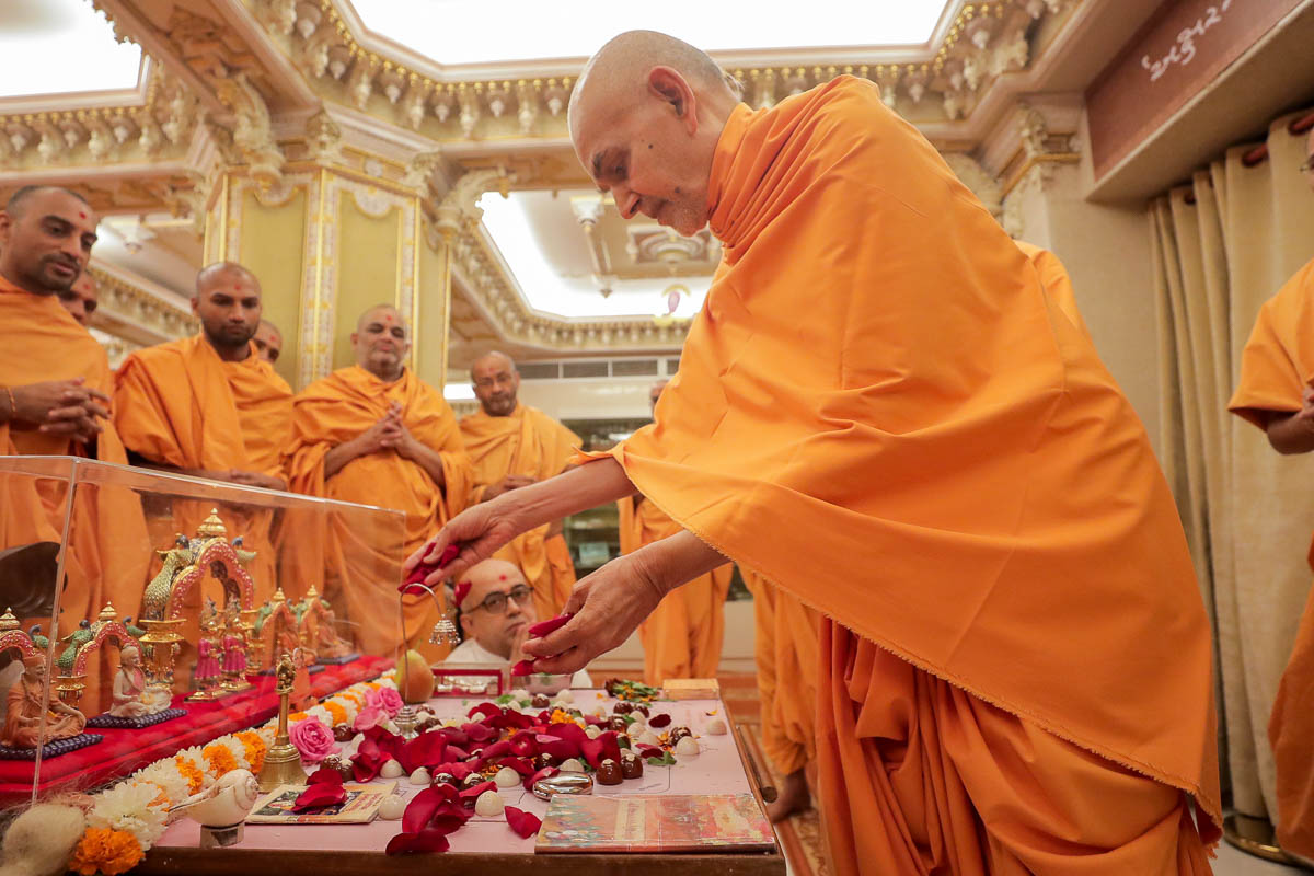 Swamishri showers flower petals in the mahapuja