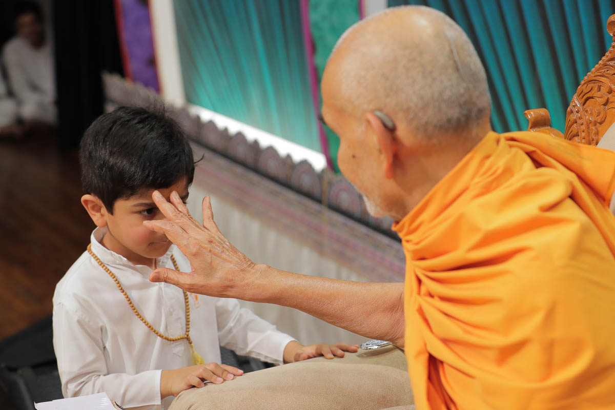 Swamishri applies chandlo to a child