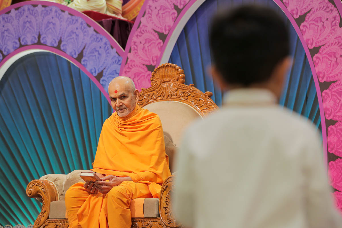 Swamishri listens to a child's recitation