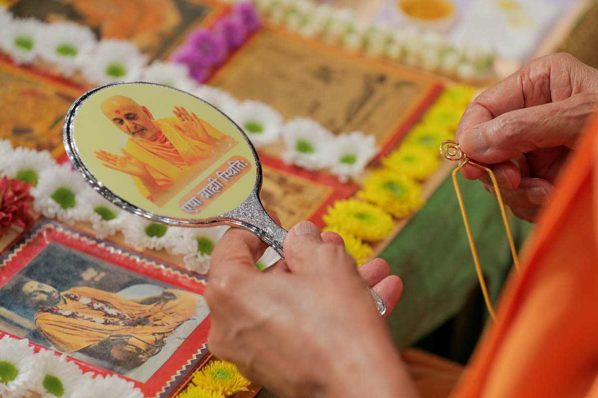 Swamishri observes a picture on the back of a mirror