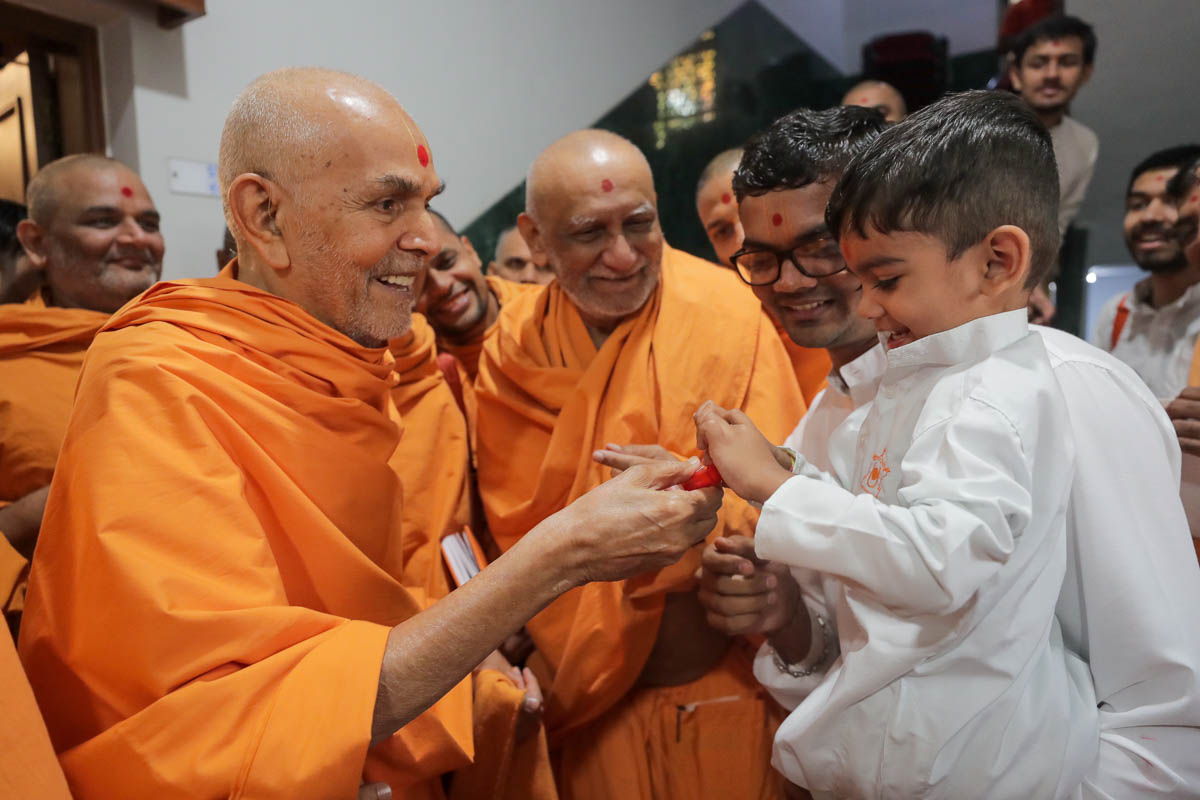 Swamishri gives a flower to a child