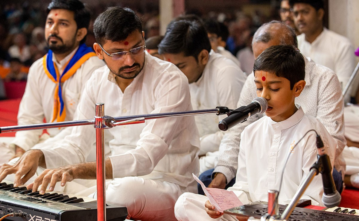 A child sings kirtans in Swamishri's daily puja