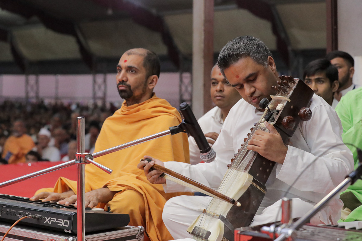 A youth plays the sarangi in Swamishri's puja