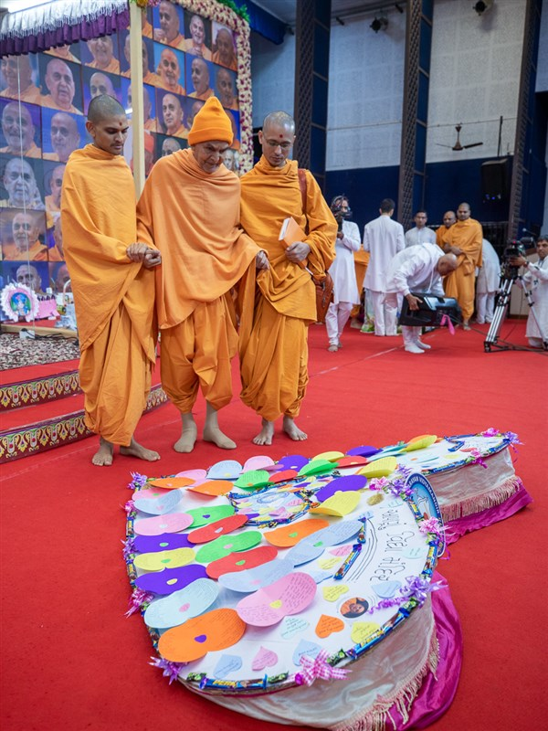 Swamishri observes a display created by students