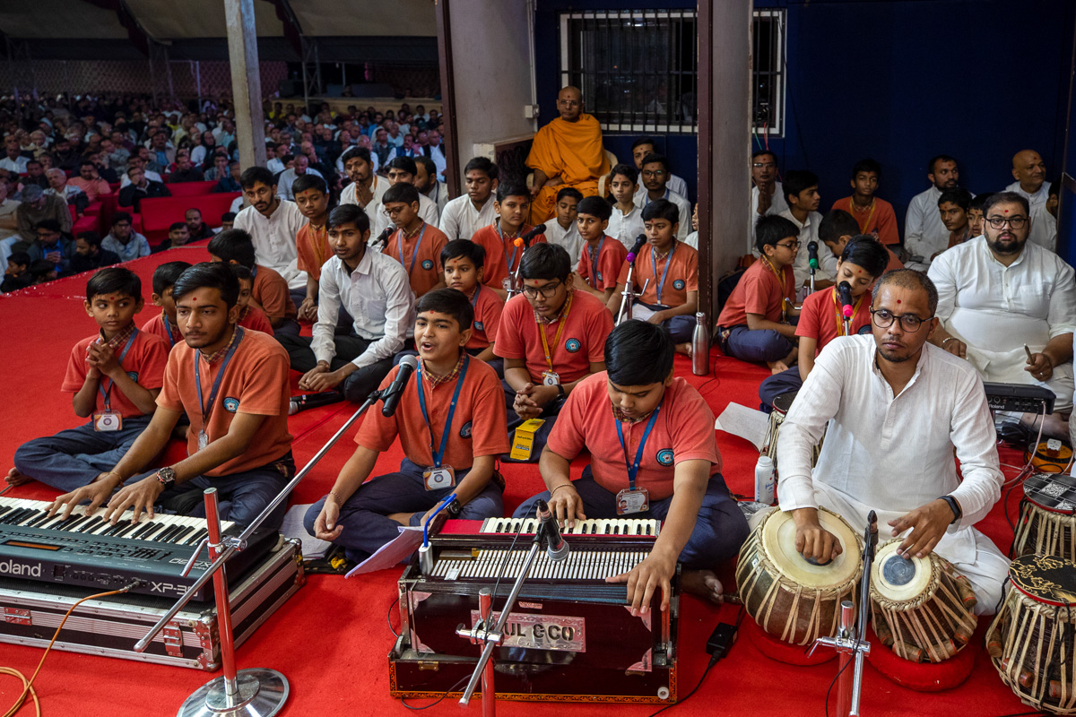 Students sing kirtans in Swamishri's morning puja