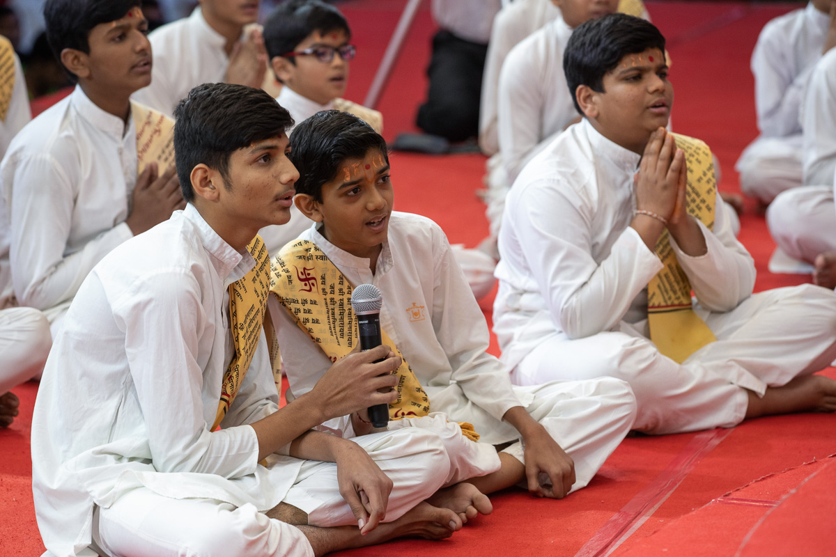 Students sing sholkas in Swamishri's daily puja