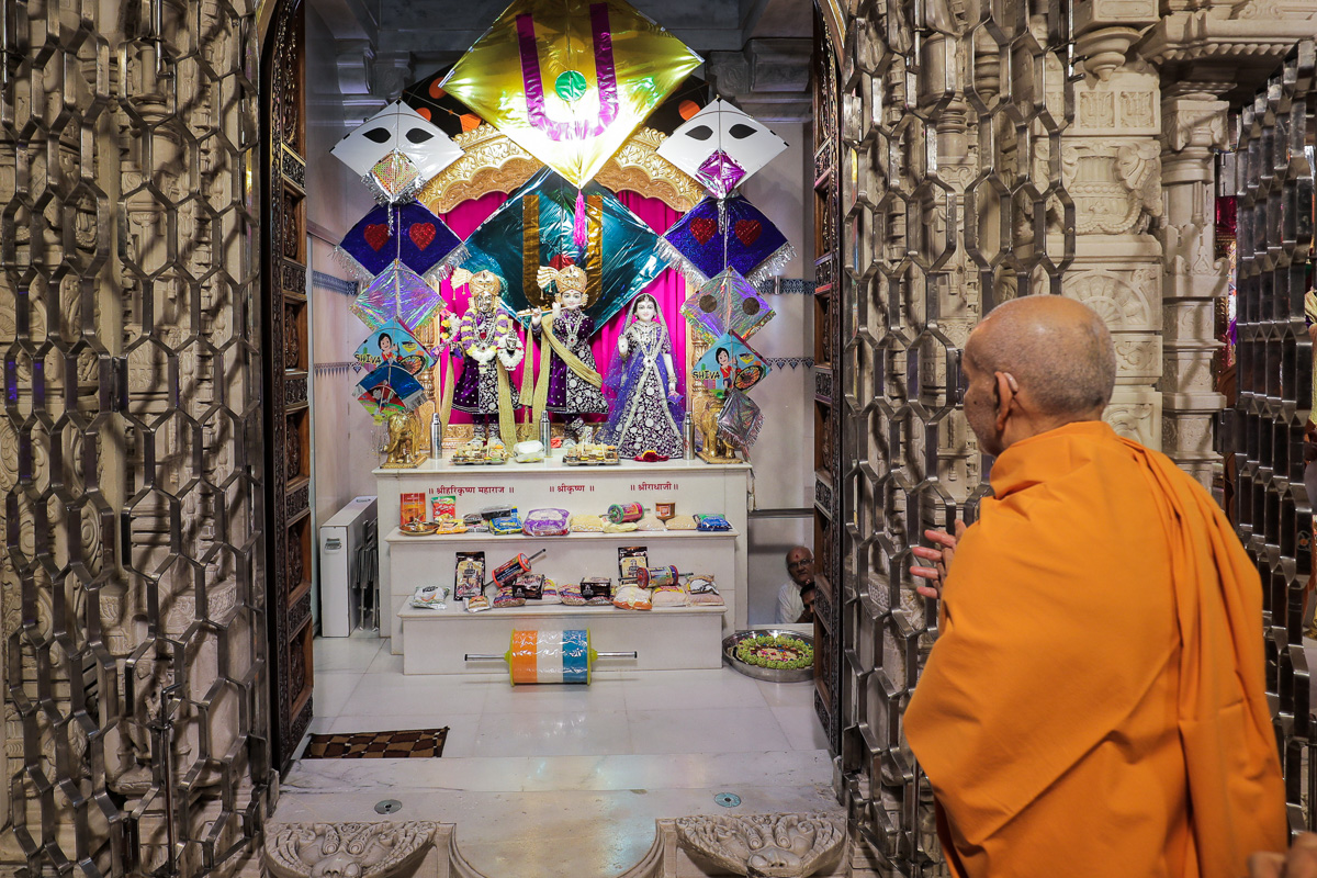 Swamishri engrossed in darshan of Shri Harikrishna Maharaj and Shri Radha-Krishana Dev
