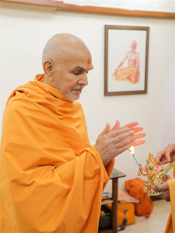 Swamishri takes aska after the arti