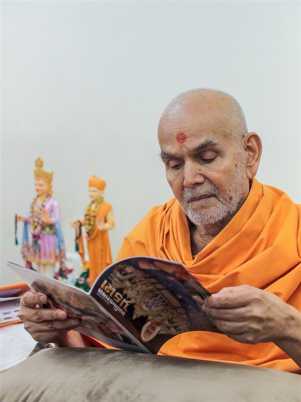 Swamishri reads the latest issue of 'Swaminarayan Prakash'