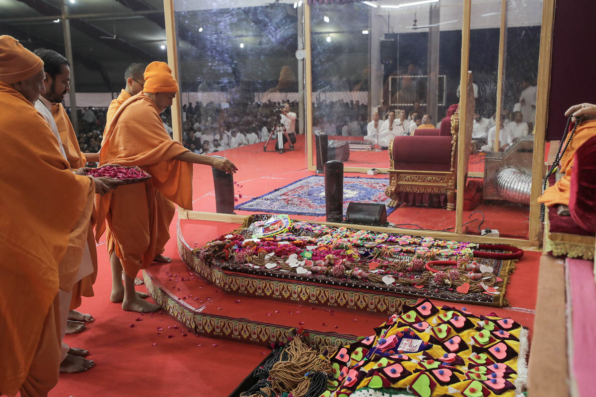Swamishri sanctifies garlands and shawls made by devotees