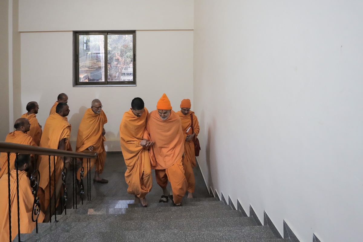 Swamishri climbs the steps towards his room