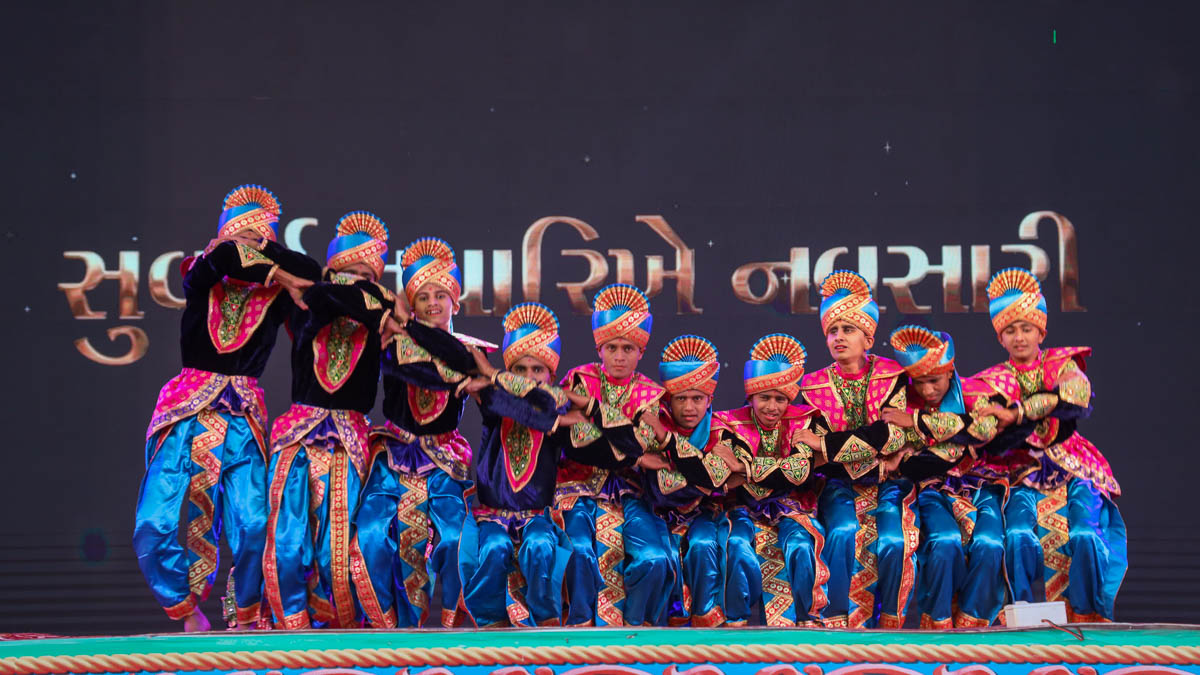 Youths perform a traditional dance during the 'Suvarna Tavarikhe Navsari' presentation in the evening satsang assembly