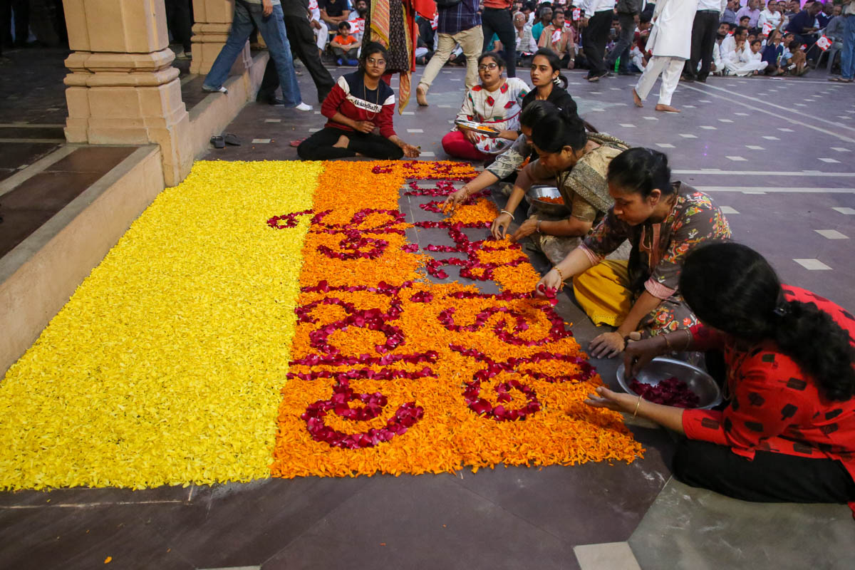 Devotees prepare a flower rangoli in the mandir campus to welcome Swamishri