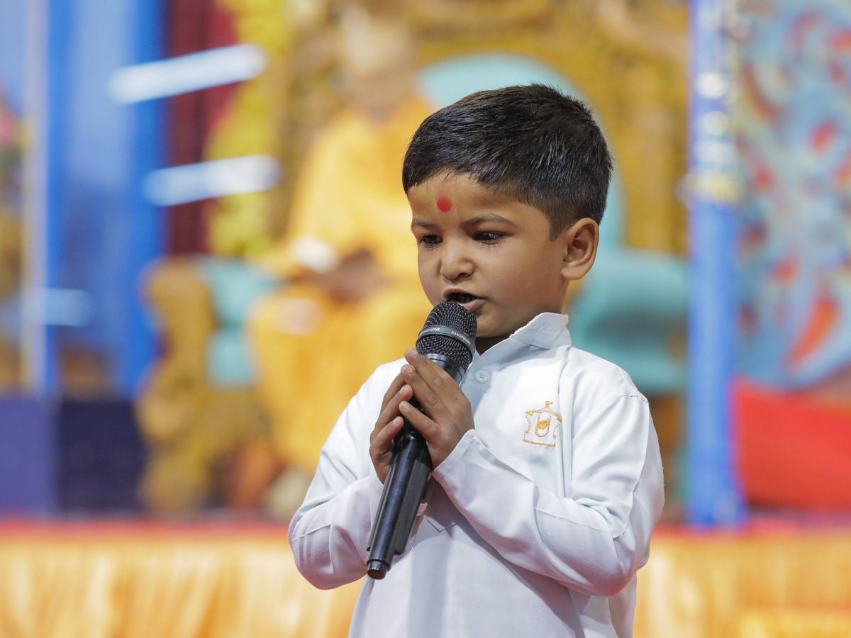A child leads everyone in reciting the sadhana mantra and daily prayer in Swamishri's puja