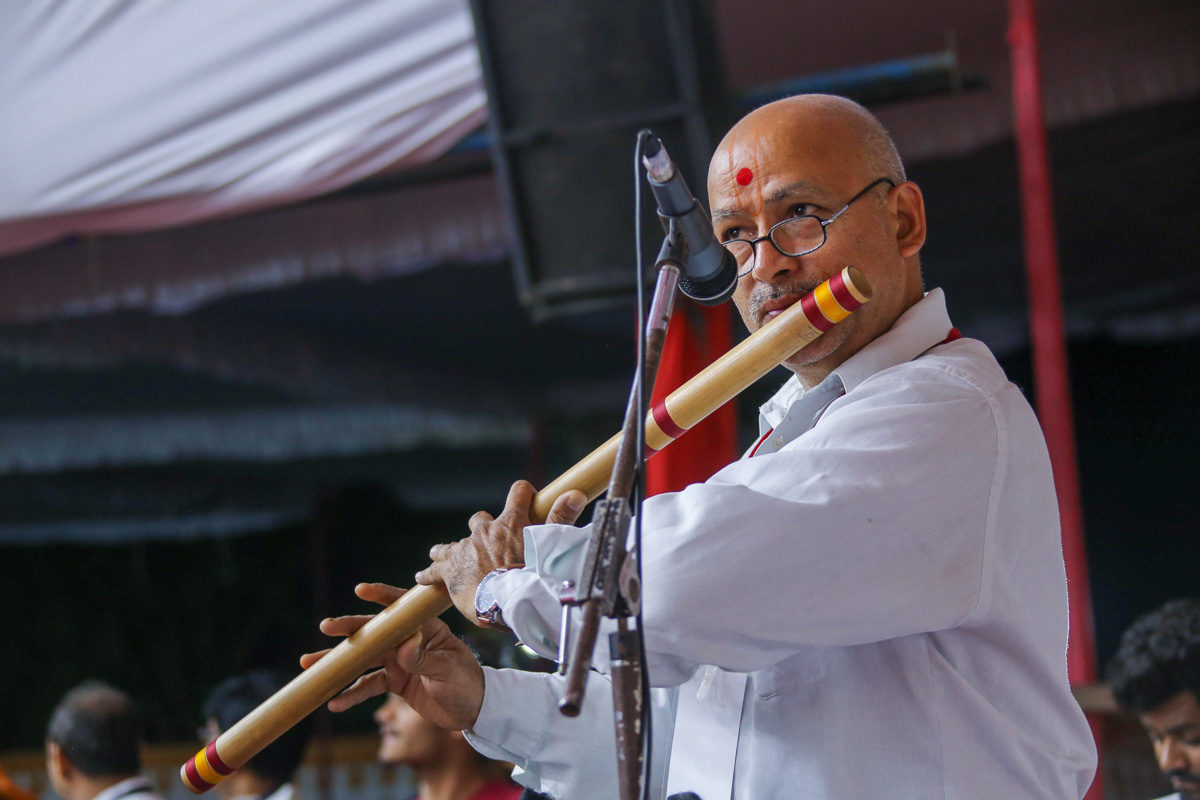 A devotee plays the flute in Swamishri's daily puja