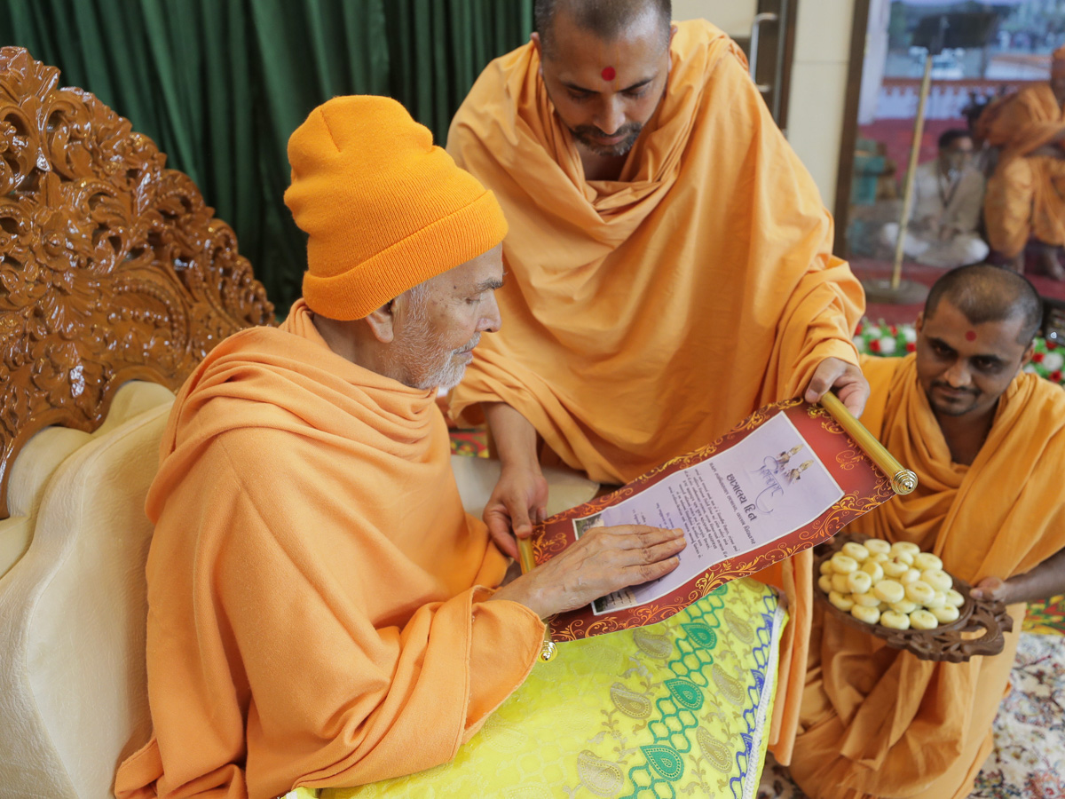 Swamishri sanctifies an invitation to the Chhatralaya Din assembly in the evening