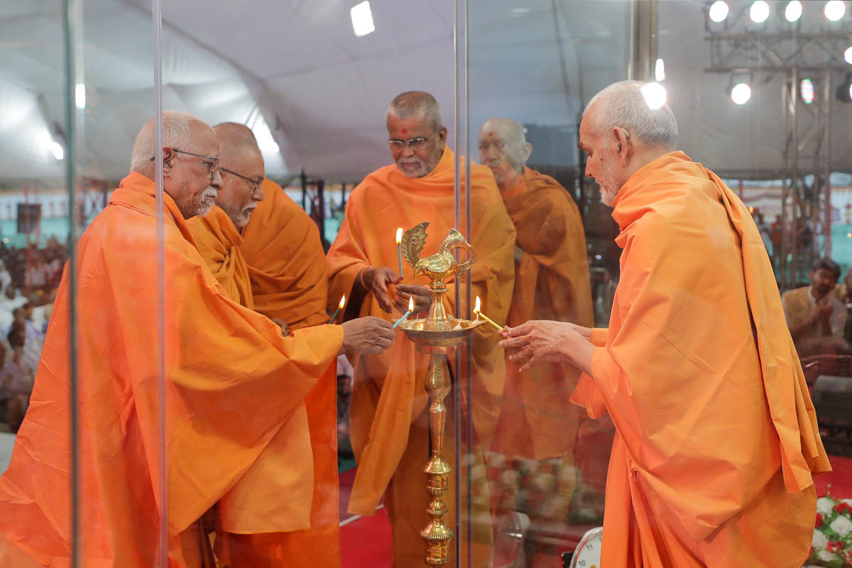 Swamishri and senior sadhus light the lamp to inaugurate the 'Parivarik Shanti Abhiyan'