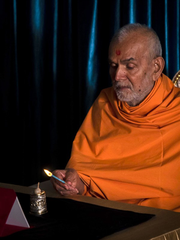 Swamishri lights a lamp to mark the fight against Covid-19