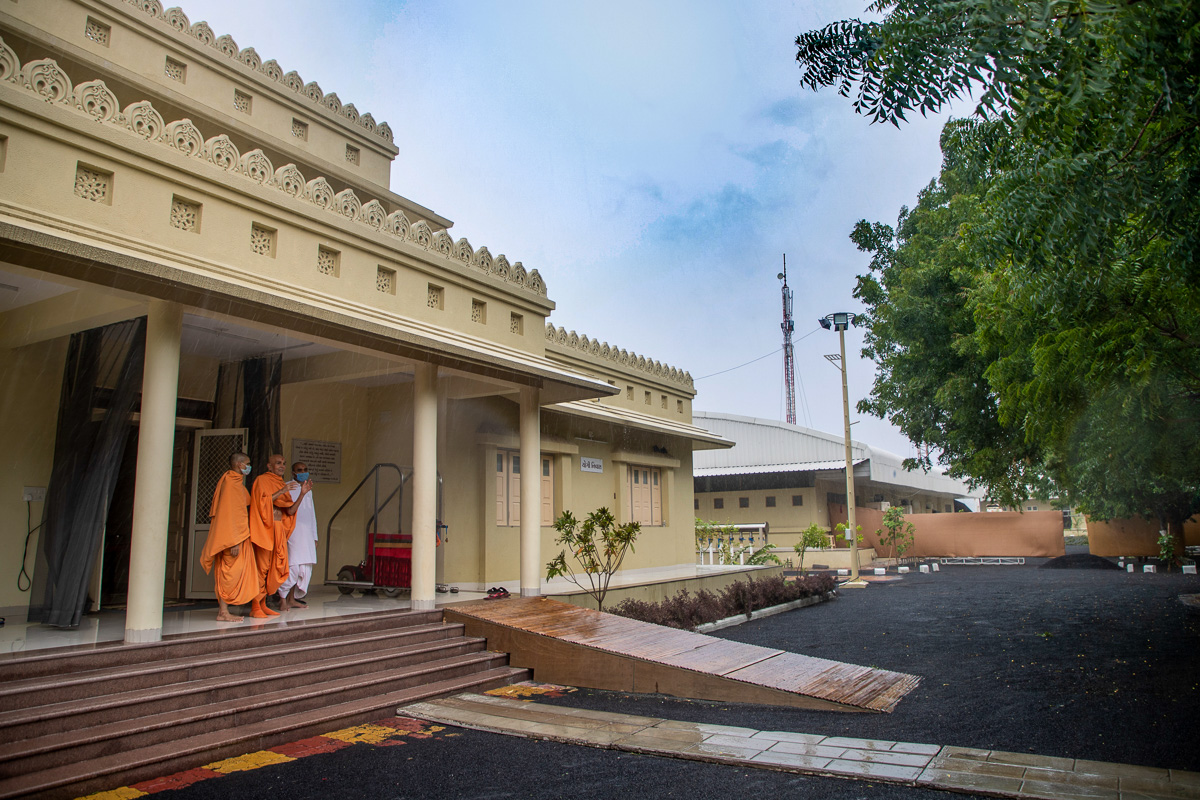 Swamishri and sadhus watch the rain