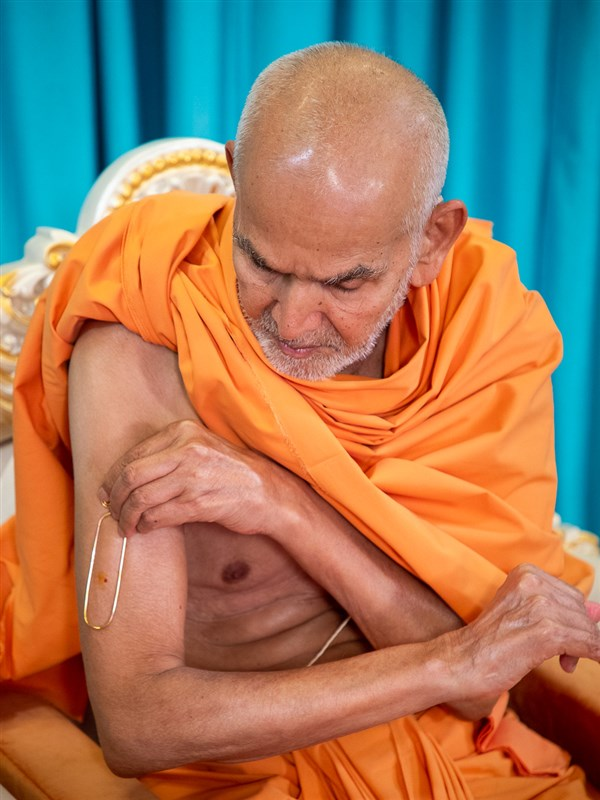 Swamishri applies a tilak on his upper arm