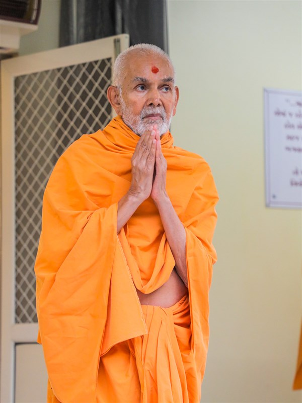 Swamishri greets all with folded hands in the evening