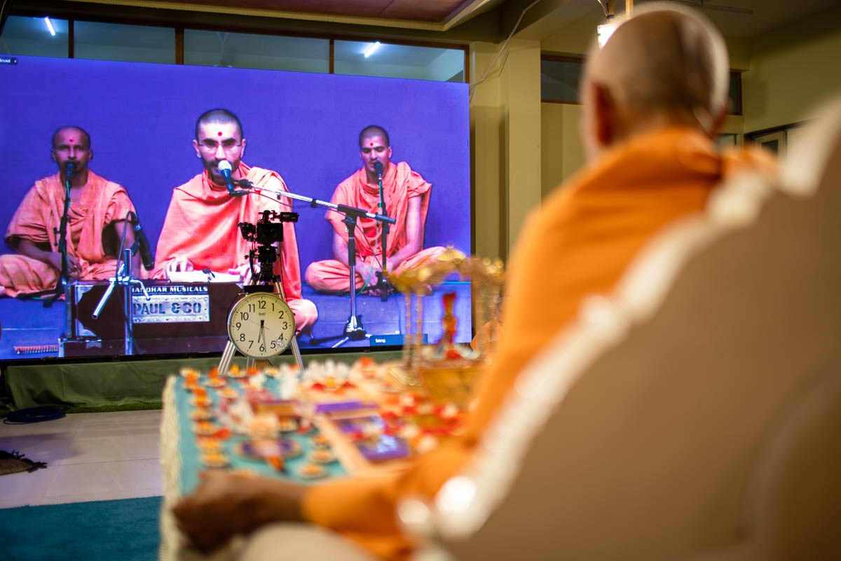 Sadhus from Sarangpur sing kirtans in Swamishri's morning puja via video conference