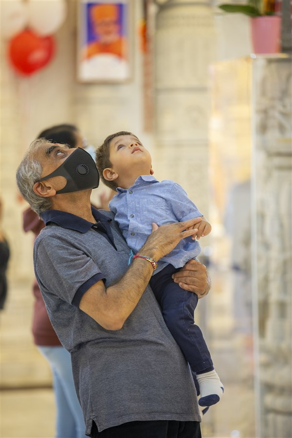 A devotee and his grandchild enjoy the beauty of the mandir