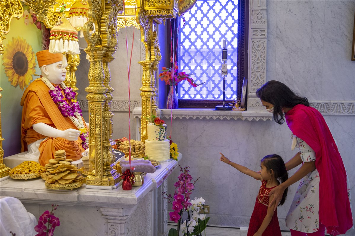 A mother and child enjoy darshan of the murtis