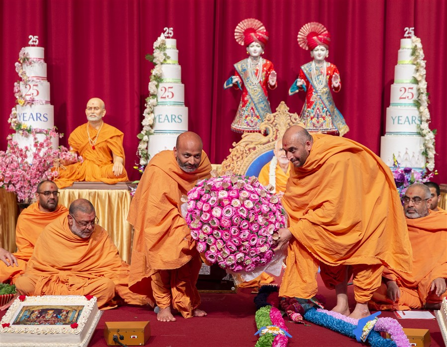 Mangaltirthdas Swami and Vishwaprakashdas Swami, among the many swamis who have been serving at London Mandir for 25 years, offered Swamishri a giant bouquet of flowers