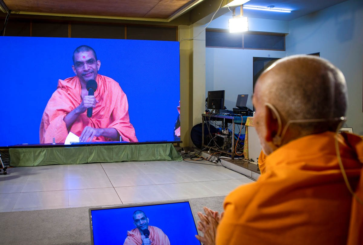 Swamishri in conversation with Adarshjivan Swami via video conference in the evening assembly