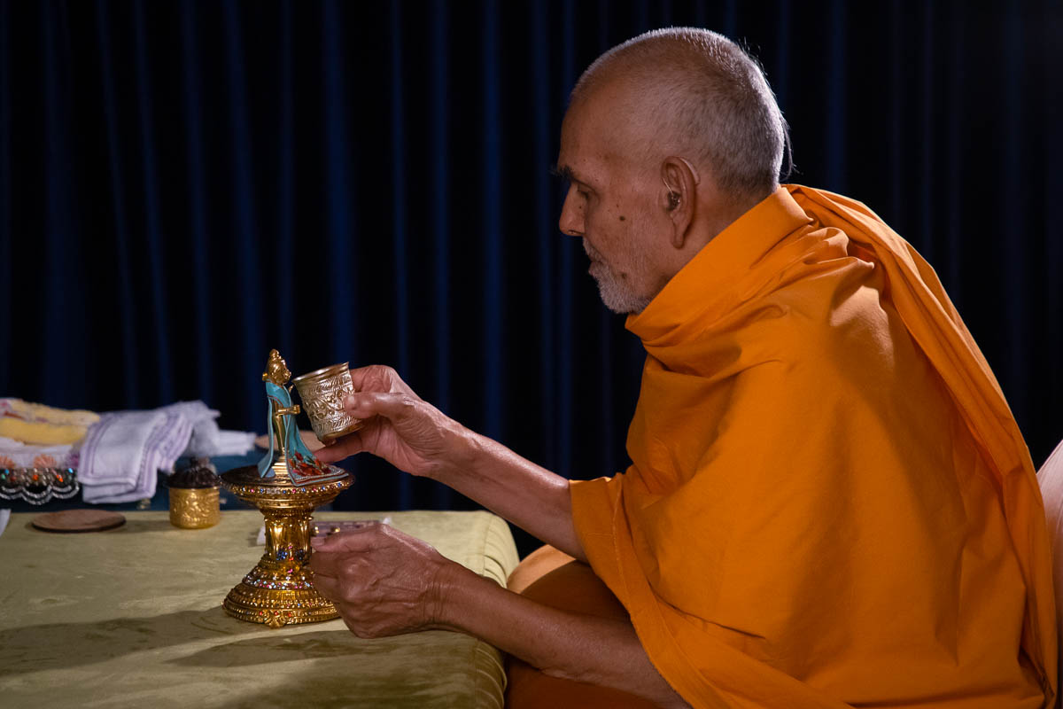 Swamishri offers water to Shri Harikrishna Maharaj