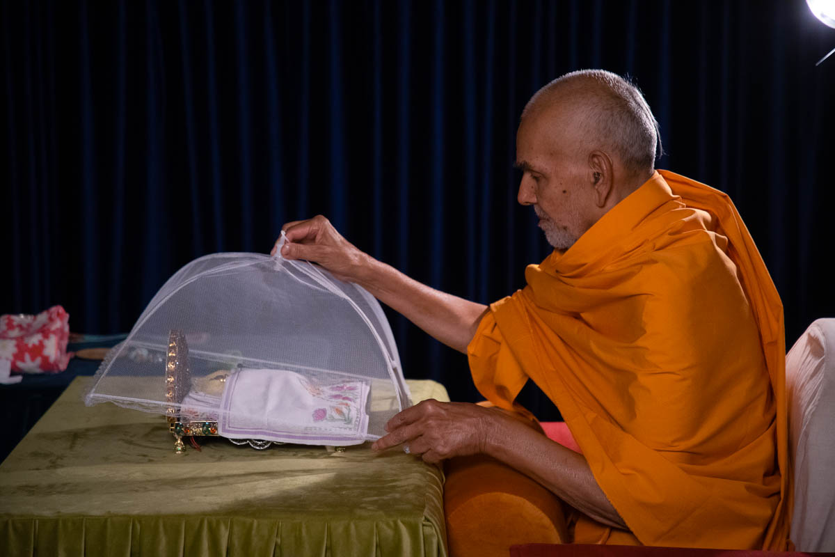 Swamishri performs night worship rituals