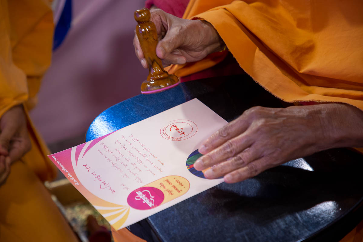 Swamishri applies a stamp of approval on a certificate