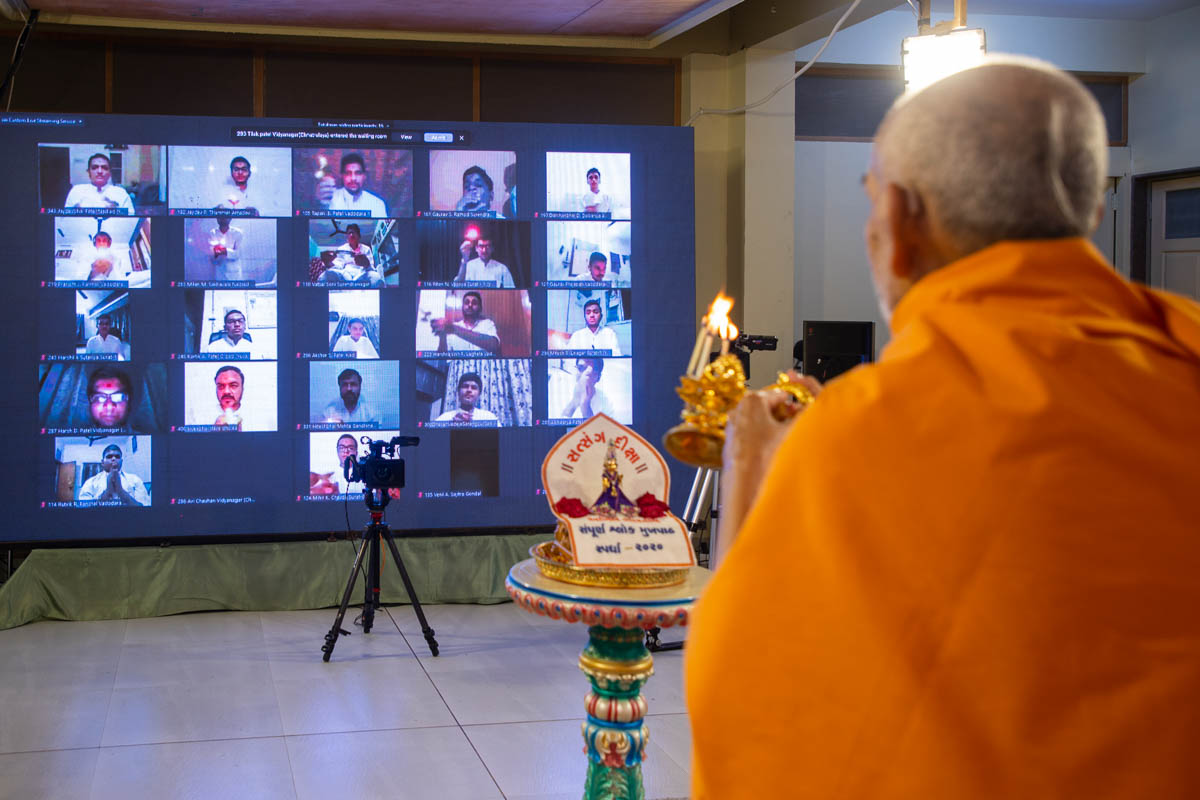 Swamishri and youths perform the arti